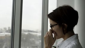 Side view of an elegant woman with short, dark hair standing by office window and adjusting her glasses with fuzzy grey stock images
