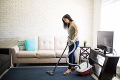 Tired young woman cleaning house dust. E view of a exhausted housewife doing daily chores of cleaning house Stock Photography
