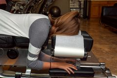 Side View of a Girl Laying on a Tilted Chiropractic Table. E view of a girl laying on a tilted chiropractic table with her head face down. There is an exercise stock photography