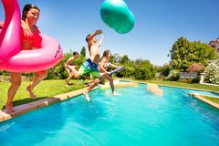 Happy boys and girls playing pool games outdoors. E view of happy teenage boys and girls with swim tools playing pool games outdoors royalty free stock photo