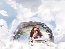 Creative inspiration of young female writer. E view of hard-working female writer using typing machine while sitting at the table with flying paper planes and royalty free stock images