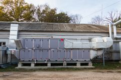 Side view of the gray industrial central conditioner with cooling coil and big condensing unit standing outdoor on the ground cove. E view of the industrial Royalty Free Stock Photography