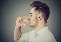 Man drinking water from glass. E view of modern man in white shirt drinking water from glass on gray background royalty free stock image