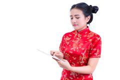 Side view portrait of Beautiful Young asian woman wear chinese dress traditional cheongsam or qipao using modern digital tablet Stock Image