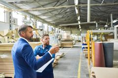 Senior Manager Touring Factory. E view portrait of handsome mature businessman touring modern factory inspecting quality of production, assisted with young royalty free stock photos