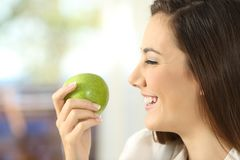 Profile of a woman holding an apple Stock Images