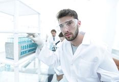Young male scientist looking at a sample in a test tube side vie. E view portrait of a scientist, uses a test tube and looking at the camera while working on Royalty Free Stock Images
