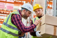 Shipping Workers in Warehouse. E view portrait of two shipping workers marking cardboard box for delivery in modern warehouse royalty free stock image