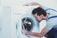Side view of repairman checking washing machine. E view of repairman checking washing machine. Repair of washing machine. White background Royalty Free Stock Photography