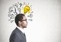 African American man glasses, question answer. E view of a young handsome African American businessman wearing glasses and a gray suit. A bright colorful light royalty free stock photos