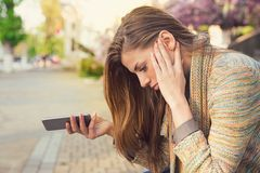 Upset woman with smartphone on street royalty free stock images