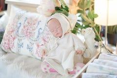 E Weichzeichnung und träumerischer Effekt eines netten schlafenden Babys - Puppe nahe bei Kaninchenstatue stockfotos