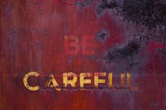 E23 Be Careful. Rusting caution sign on ancient boxcar stock images