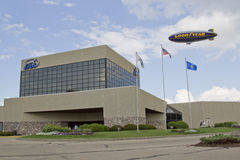 EAA Headquarters Building and GoodYear Blimp. OSHKOSH, WI - JULY 27: GoodYear Blimp Spirit of above EAA Headquarters Building at the 2012 AirVenture at EAA on royalty free stock photography