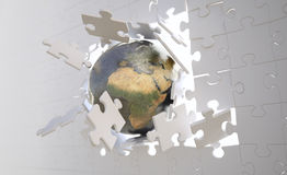 Eaarth breaking through jigsaw wall Stock Image