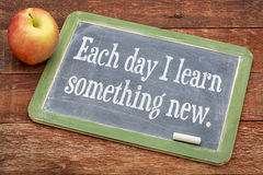 Each day I learn something new. Positive words on a slate blackboard against red barn wood Royalty Free Stock Image