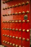 Richly decorated red wooden door with decoration in the Forbidden City, Beijing, China. royalty free stock photos