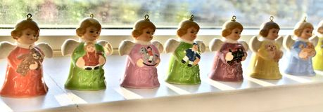 Vintage, Miniature and Colourful Angel Bells are Rear Lite by Heavenly Sunshine on a Shelve during Christmas Season. Each precious angelic winged ornament is Stock Photo