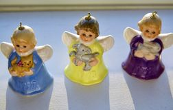 Vintage, Colourful and Miniature Angel Bells are Rear Life by Heavenly Sunshine on a Shelve during Christmas Season. Each precious angelic winged ornament is Royalty Free Stock Photography