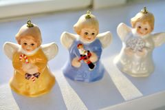 Colourful, Miniature and Vintage Angel Bells are Rear Life by Heavenly Sunshine on a Shelve during Christmas Season. Each precious angelic winged ornament is Stock Photography