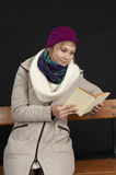 Eading young woman in winter clothes on black Stock Photos