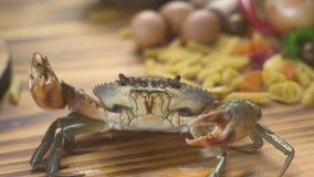 Eafoodconcept Leef krab op keukenlijst aangaande Italiaanse deegwarenachtergrond Overzeese krab voor het koken van zeevruchtensch stock footage
