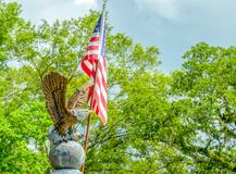 Eagel en el globo con los árboles de la bandera americana y las nubes oscuras Fotos de archivo