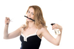 Eager beautician. Funny portrait of young smiling attractive blond beautician woman holding comb in her mouth, hairdresser scissors and spray bottle in her arms Royalty Free Stock Images