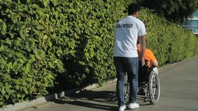 Eager beaver volunteer walking with a wheelchaired man. More activities in life. Helpful eager beaver volunteer walkingith a wheelchaired man while enjoying a stock footage