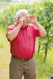 Eager to know. Curious senior man putting on his glasses to check out the situation Royalty Free Stock Photos