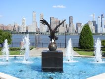 Eagle en bronze majestueux dans une fontaine d'eau contre un horizon de New York City Images libres de droits