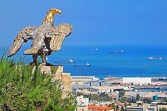 Eagle garde la porte aux jardins de Bahai et donne sur le paysage urbain et la côte de Haïfa image libre de droits