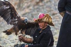 Eagle Hunter an der traditionellen Kleidung, bei der Jagd zu den Hasen, die einen Steinadler, in den Bergen West-Mongolei halten Stockfoto