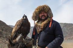 Eagle Hunter an der traditionellen Kleidung, bei der Jagd zu den Hasen, die einen Steinadler, in den Bergen West-Mongolei halten Stockbild