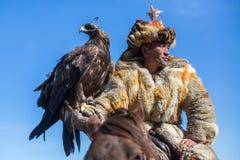 Eagle Hunter an der traditionellen Kleidung, bei der Jagd zu den Hasen, die einen Steinadler, in den Bergen West-Mongolei halten Lizenzfreie Stockbilder