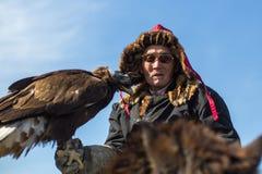 Eagle Hunter an der traditionellen Kleidung, bei der Jagd zu den Hasen, die einen Steinadler, in den Bergen West-Mongolei halten Stockbilder