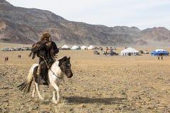 Eagle Hunter an der traditionellen Kleidung, mit einem Steinadler auf seinem Arm während des jährlichen nationalen Wettbewerbs mi Lizenzfreies Stockfoto