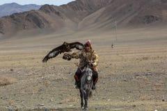 Eagle Hunter an der traditionellen Kleidung, mit einem Steinadler auf seinem Arm während des jährlichen nationalen Wettbewerbs mi Stockfotos