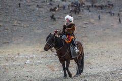 Eagle Hunter dorato kazako ad abbigliamento tradizionale, con un'aquila reale sul suo braccio Fotografie Stock
