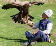 Eagle Hunter hält seine Adler und sitzt aus den Grund Stockfotos
