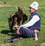 Eagle Hunter hält seine Adler und sitzt aus den Grund Lizenzfreies Stockbild