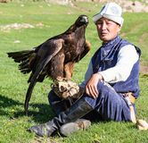 Eagle Hunter holds his eagles, sitting on the ground Royalty Free Stock Images