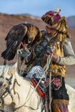 Eagle Hunter while hunting to the hare with a golden eagles on his arms in the mountains of Bayan-Olgii aimag. SAGSAY, MONGOLIA - SEP 28, 2017: Eagle Hunter Royalty Free Stock Images