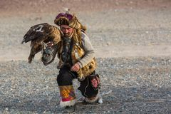 Eagle Hunter while hunting to the hare with a golden eagles on his arms in the mountains of Bayan-Olgii aimag. SAGSAY, MONGOLIA - SEP 28, 2017: Eagle Hunter Stock Photography