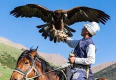 Eagle Hunter rymmer hans örnar på hästrygg royaltyfri foto