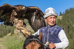 Eagle Hunter rymmer hans örnar på hästrygg, ordnar till för att ta flyg arkivfoton