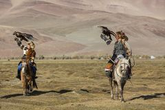 Eagle Hunter teaches her young daughter hunting with birds of prey to the hare in desert mountain of Western Mongolia. SAGSAY, MONGOLIA - SEP 28, 2017: Eagle Royalty Free Stock Image