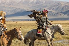 Eagle Hunter teaches her young daughter hunting with birds of prey to the hare in desert mountain of Western Mongolia. SAGSAY, MONGOLIA - SEP 28, 2017: Eagle Royalty Free Stock Photos