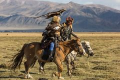 Eagle Hunter teaches her young daughter hunting with birds of prey to the hare in desert mountain of Western Mongolia. SAGSAY, MONGOLIA - SEP 28, 2017: Eagle Royalty Free Stock Photo