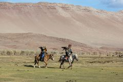 Eagle Hunter teaches her young daughter hunting with birds of prey to the hare in desert mountain of Western Mongolia. SAGSAY, MONGOLIA - SEP 28, 2017: Eagle Stock Images